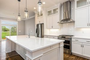 A luxury custom kitchen design featuring oversized island and stainless steel appliances.